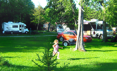 Our Curtis MI Lakeside Campground includes water, electric, bathhouse, dump station, picnic table, fire pit, and a sandy beach.
